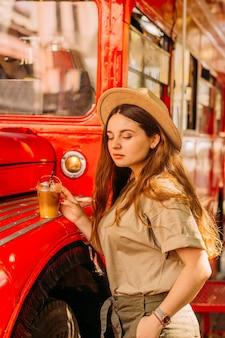 赤いバスの横にある帽子をかぶった女の子