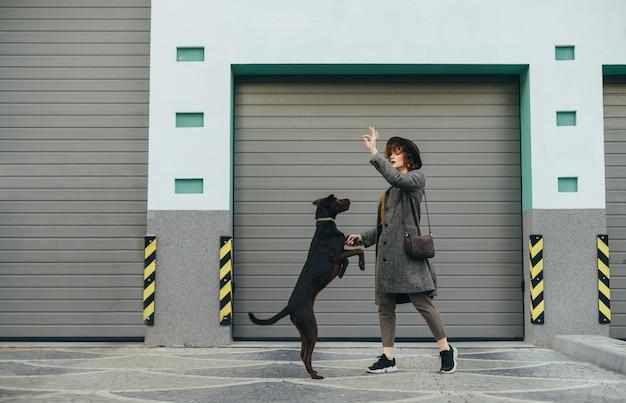 Девушка в шляпе играет с собакой на фоне серой стены