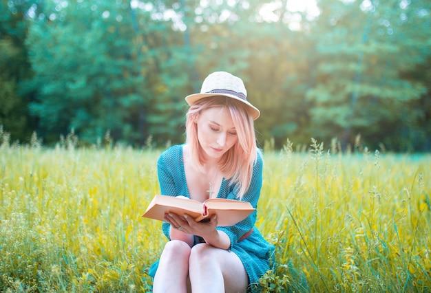 帽子をかぶった少女は新鮮な空気の中で本を読みます。