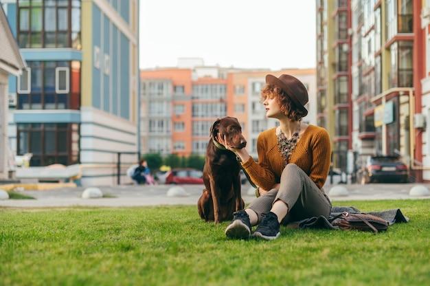 Девушка в шляпе сидит с красивой коричневой собакой на лужайке