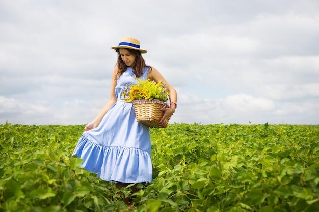 花のバスケットと緑のフィールドに立っている帽子の少女