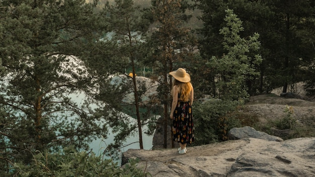 Девушка в шляпе путешествует по красивым местам планеты, летний день