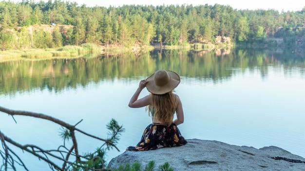 모자를 쓴 소녀는 여름날 행성의 아름다운 곳으로 여행합니다.