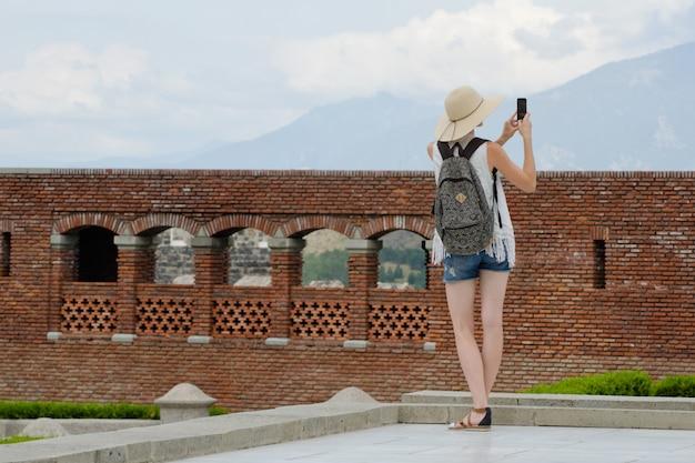 Девушка в шляпе с рюкзаком фотографирует старую крепость. вид со спины