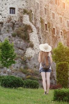 要塞の近くに立っているバックパックを持つ帽子の少女。背面図