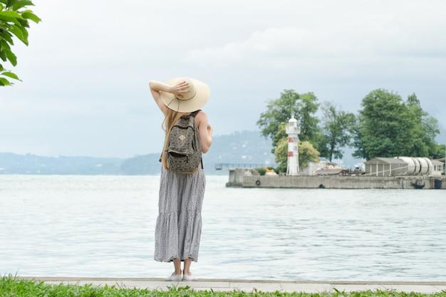 Девушка в шляпе с рюкзаком стоит на пирсе у моря. горы и маяк. вид со спины