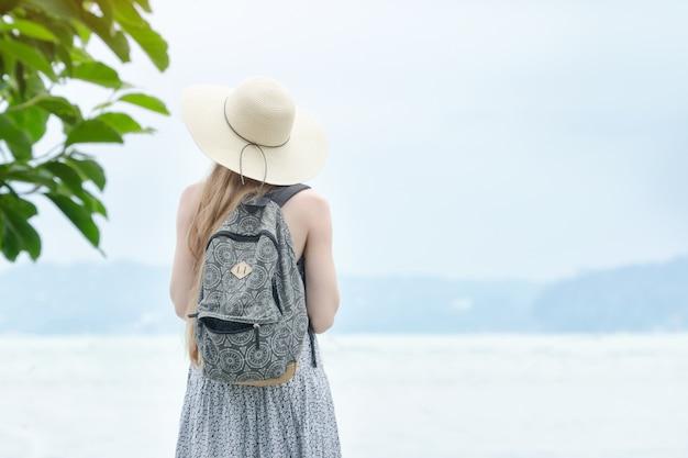 Девушка в шляпе с рюкзаком стоит на пирсе у моря.