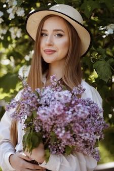 Девушка в шляпе с букетом сирени. летняя прогулка в парке. красивый макияж. студент идет на свидание.