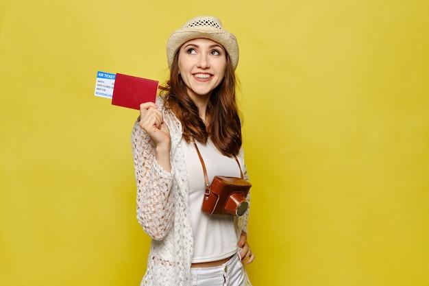 Девушка в шляпе с ретро камерой держит паспорт с билетами на самолет на желтом фоне. копировать пространство