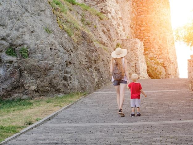 Девушка в шляпе с маленьким сыном гуляют у стен крепости