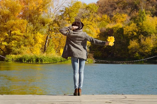 ドックに立っている手に葉を持つ帽子の少女。秋、晴れ。背面図
