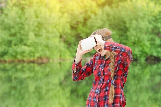 自然の上の仮想現実のヘルメットの少女。