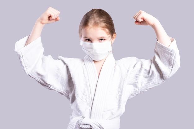 着物柔道の女の子。強さを示します。灰色の背景に分離。高品質の写真