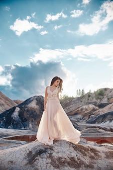 Девушка в голубом платье, стоя на ветру с горами на заднем плане. чистая и безупречная красота, сказочный образ женщины.