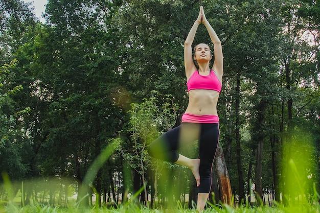 Девушка в легком спортивном костюме занимается йогой в парке днем летом