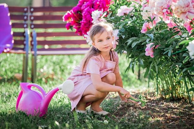 庭で夏に牡丹の世話をするリネンのドレスを着た女の子