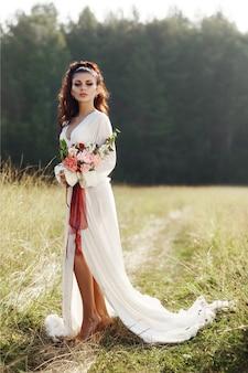 長いドレスを着た少女が花輪を頭に、花束を手に持って畑に立っている。村の秋の夕陽の光に照らされた美しい女性。田舎の生活とファッション