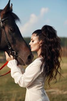長いドレスを着た少女が馬のそばに立ち、美しい女性が馬をなでて、秋に野外で手綱を握ります。田舎の生活とファッション、高貴な馬
