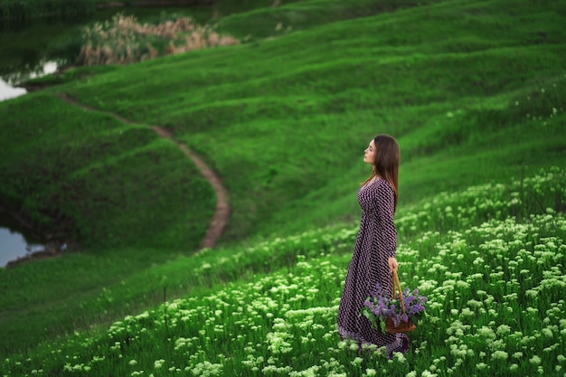 散歩に籐のかごを持つロング ドレスの女の子
