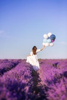 Девушка в длинном белом платье гуляет по лавандовому полю. вид со спины. в руках большой букет воздушных шаров.
