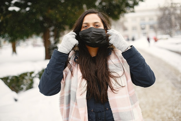 마스크에 소녀입니다. 따뜻한 옷을 입고 인도 여자. 겨울에 거리에 아가씨.