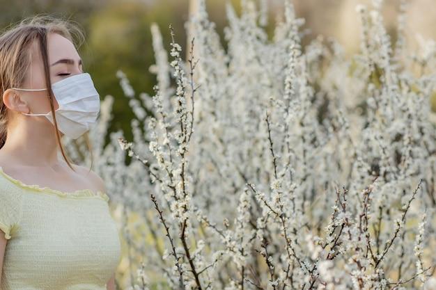 Девушка в медицинской маске. девушка весной среди цветущего сада.