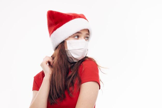 Девушка в медицинской маске новогодней одежде смотрит в сторону светлом фоне. фото высокого качества