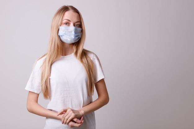 회색 벽에 의료 마스크 소녀