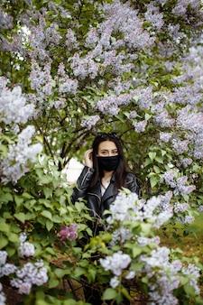 咲くライラックの上に医療マスクの女の子。黒いマスク。ウイルス、インフルエンザに対する保護。コロナウイルス防止。コロナウイルスの流行。庭の木の香り春のアレルギー。