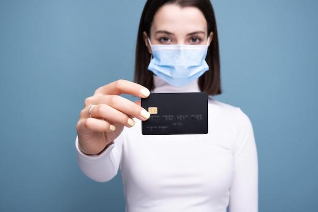 Девушка в медицинской маске с банковской картой на синей стене.