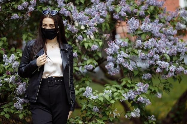Девушка в медицинской маске с цветущей сиренью. черная маска. защита от коронавируса. эпидемия коронавируса. аромат дерево в саду весенняя аллергия