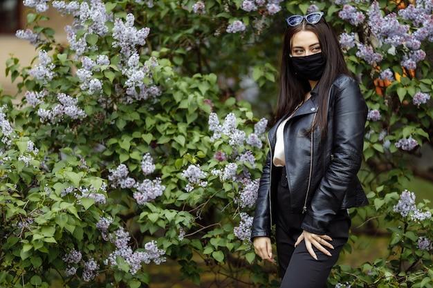 Девушка в медицинской маске с цветущей сиренью в парке. черная маска. коронавирус защита. весенняя аллергия