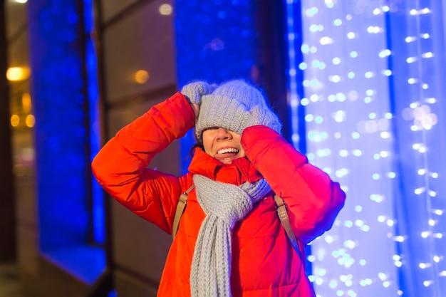 밤 도시 눈송이에서 소녀 크리스마스 도시의 불빛입니다. 크리스마스와 겨울 휴가 개념입니다.