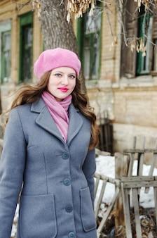 분홍색 베레모와 회색 파란색 코트를 입은 소녀가 구시 가지 거리를 따라갑니다.