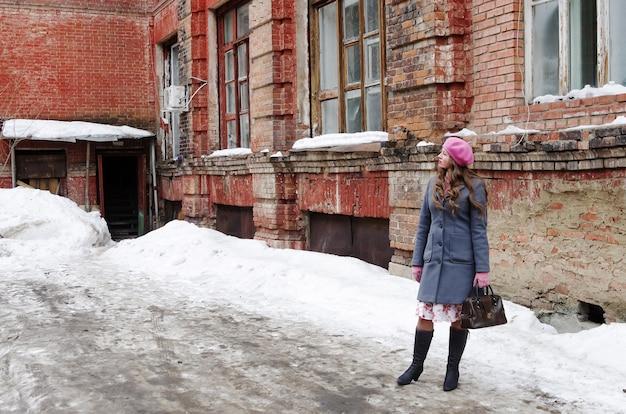 핑크 베레모 소녀와 오래된 집 마당에 서있는 grayblue 코트