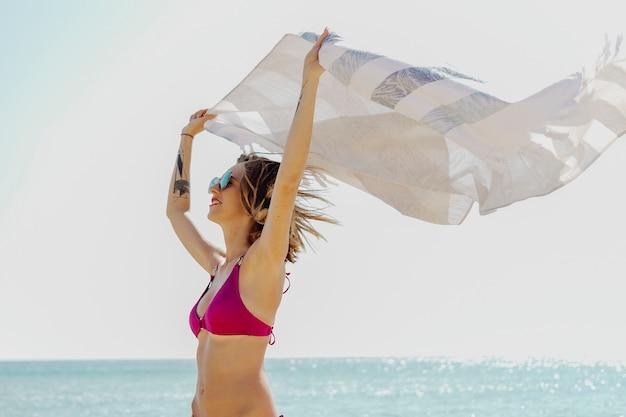 바람이 부는 해변을 즐기는 분홍색 비키니 소녀