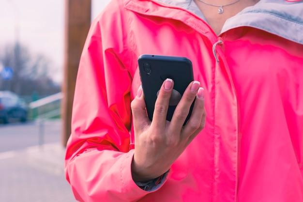 ピンクのジャケットを着た女の子がスマートフォンを手に持っています。モックアップテクノロジー。