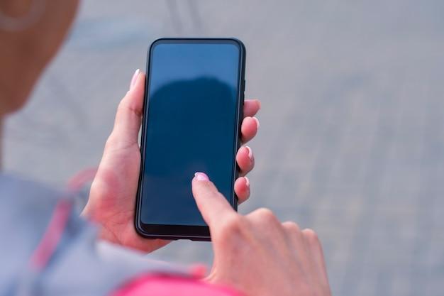 ピンクのジャケットを着た女の子は、スマートフォンのモックアップを手に持っています。モックアップテクノロジー。