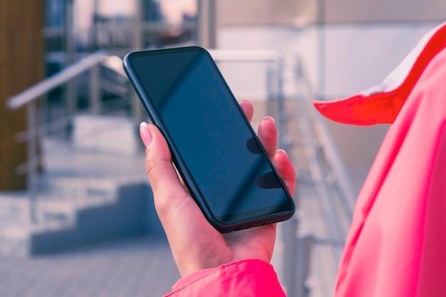 ピンクのジャケットを着た女の子がスマートフォンのモックアップを手に持っています。モックアップテクノロジー。