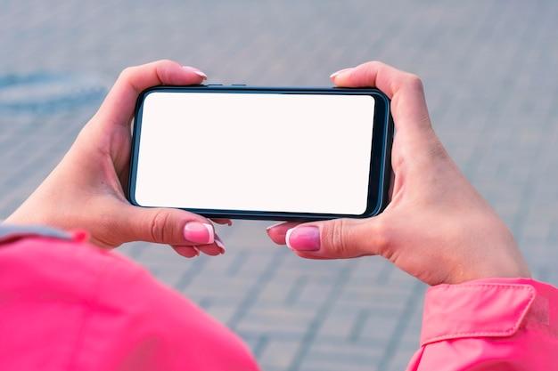 ピンクのジャケットの女の子は、手に白い画面でスマートフォンのモックアップを保持しています。モックアップテクノロジー。