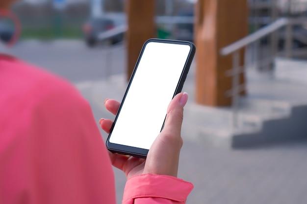 ピンクのジャケットを着た女の子は、手に白い画面でスマートフォンのモックアップを保持しています。モックアップテクノロジー。