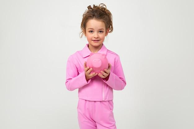 ピンクのスーツの女の子が空白の白い壁に貯金箱を保持します