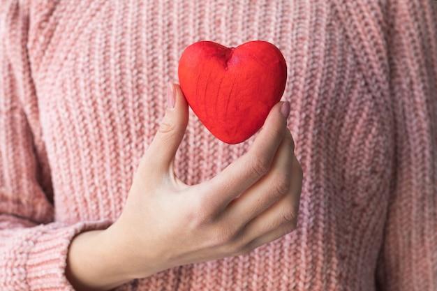 ピンクのセーターを着た女の子は、愛の宣言の概念である赤いハートを手に持っています。