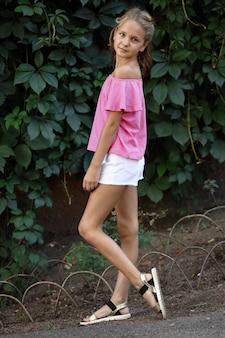 ピンクのtシャツと野生ブドウの葉の白いショートパンツの女の子。クローズアップポートレート