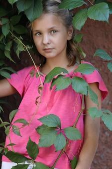野生のブドウの葉にピンクのtシャツを着た女の子。クローズアップポートレート