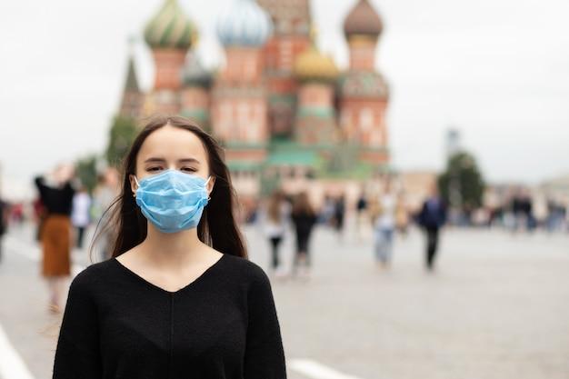 コロナウイルスの間に赤い四角にモスクワの保護マスクの女の子