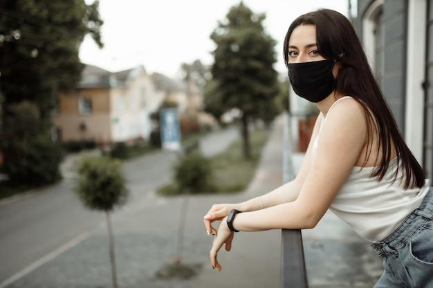 バルコニーの保護マスクの女の子は空の街を見る