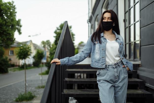 Девушка в защитной маске на балконе смотрит на пустой город