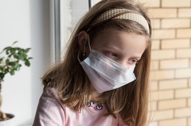 の顔に防護マスクの女の子が窓際に座っています。外科医の保護マスクの子供。検疫を中止、学校なし。