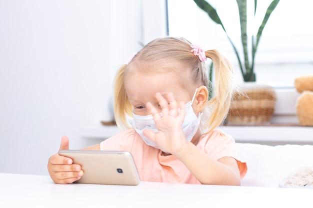 휴대 전화를 사용하여 보호 의료 마스크에 소녀, 화상 통화를위한 스마트 폰, 친척과 이야기, 소녀는 집에 앉아, 온라인 컴퓨터 웹캠, 화상 통화를합니다.